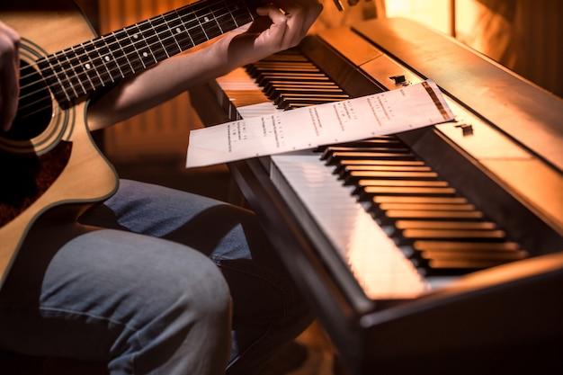 Homem tocando violão e close-up de piano Foto gratuita