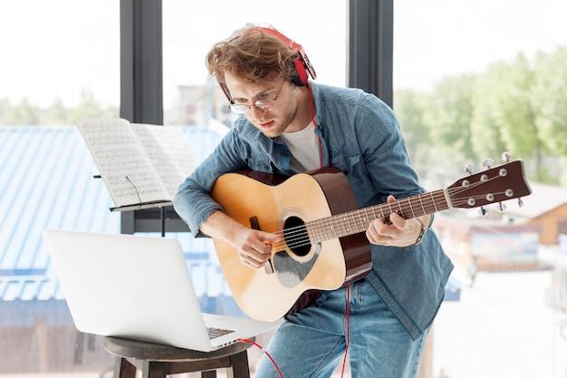 Homem tocando violão em casa Foto gratuita