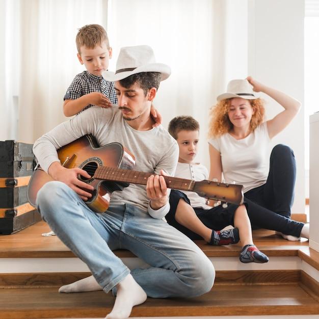 Homem tocando violão para sua família em casa | Foto Grátis