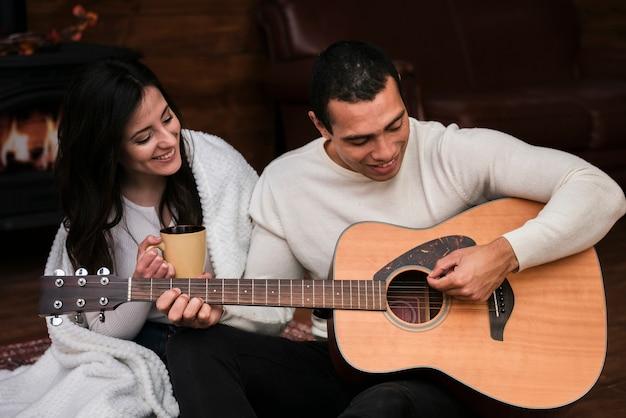 Homem tocando violão para sua namorada Foto gratuita