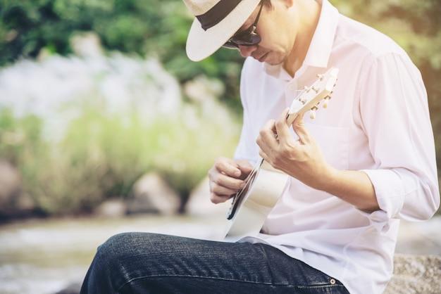 Homem tocar cavaquinho novo para o rio Foto gratuita