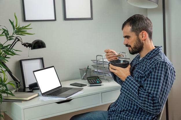 Homem tomando café da manhã enquanto trabalha em casa Foto gratuita