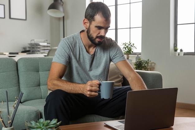 Homem tomando café e trabalhando em casa no laptop Foto gratuita