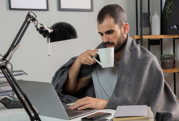 Homem tomando café enquanto trabalha em casa Foto gratuita