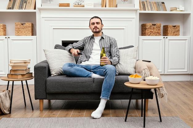 Homem tomando uma cerveja e assistindo tv dentro de casa Foto gratuita