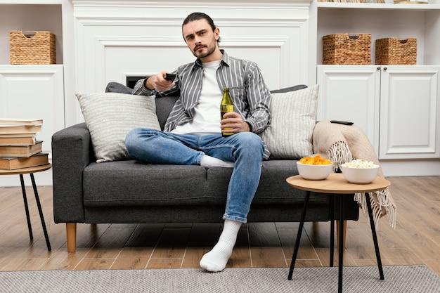 Homem tomando uma cerveja e assistindo tv Foto gratuita