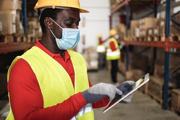 Homem trabalhador africano usando tablet dentro do armazém, usando máscara de segurança - foco no rosto Foto Premium