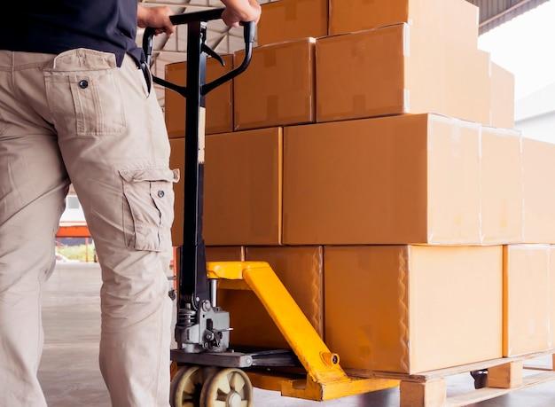 Homem trabalhador descarregando caixas de pacote de remessa em paletes com paleteira de mão Foto Premium