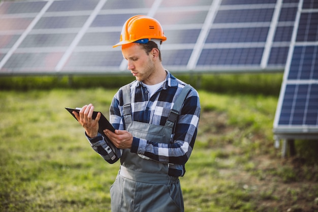 Homem trabalhador no firld pelos painéis solares Foto gratuita