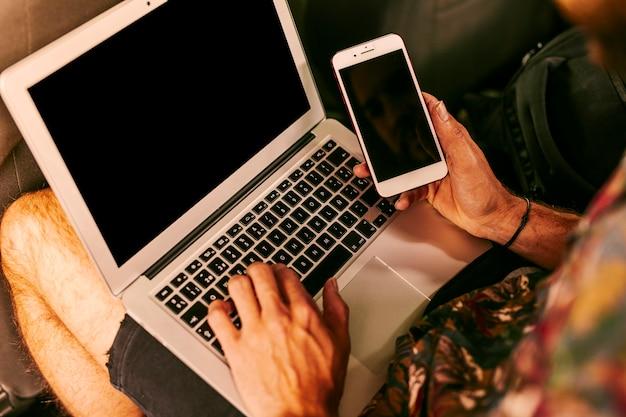 Homem, trabalhando, com, laptop, e, smartphone Foto gratuita