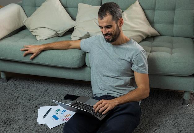 Homem trabalhando em um laptop ao lado do sofá Foto gratuita