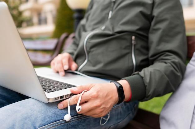 Homem trabalhando no laptop fora com fones de ouvido Foto gratuita