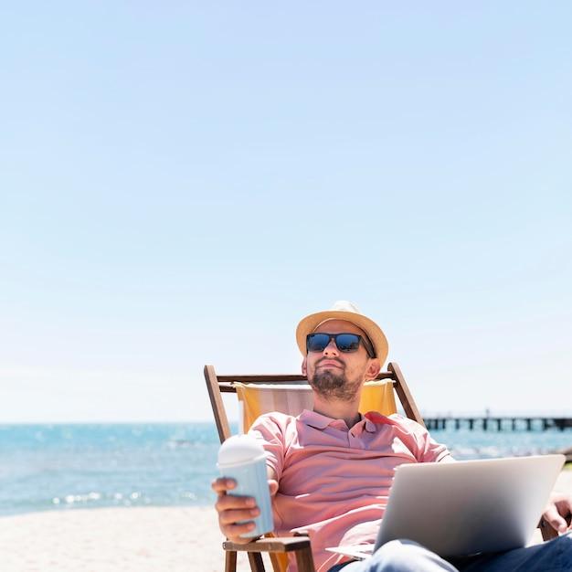 Homem trabalhando no laptop na praia enquanto desfruta de bebida Foto Premium