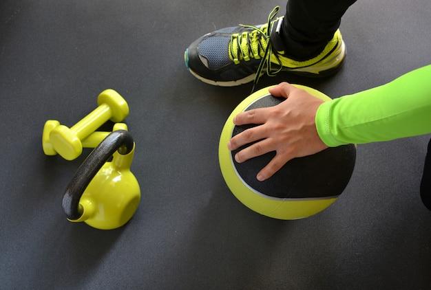 Homem treinando com kettlebell e medicine ball em casa Foto Premium