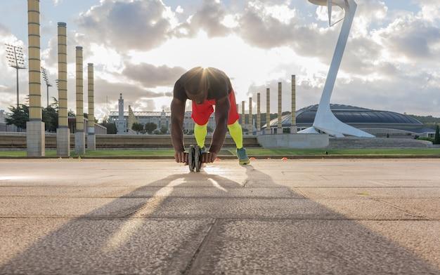 Homem treinando os músculos abdominais com uma roda no parque Foto Premium