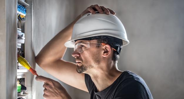 Homem, um técnico elétrico trabalhando em um painel de distribuição com fusíveis. instalação e conexão de equipamentos elétricos. Foto gratuita