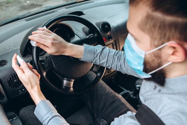 Homem usa desinfetante enquanto dirigia o carro. precauções durante a epidemia de coronavírus. homem com máscara médica no carro. Foto Premium