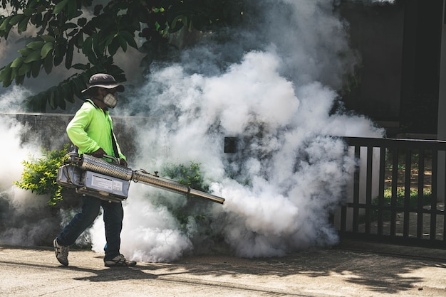 Homem usando a máquina de nebulização para controlar perigosos mosquitos Foto Premium