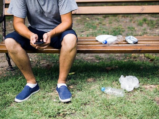 Homem, usando, cellphone, sentando, ligado, banco, perto, lixo plástico, parque Foto gratuita