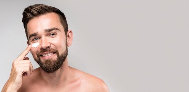 Homem usando creme facial com espaço de cópia Foto gratuita