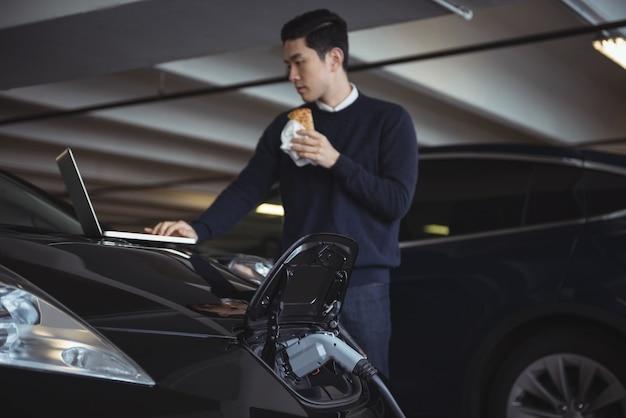 Homem usando laptop enquanto carrega o carro elétrico Foto gratuita