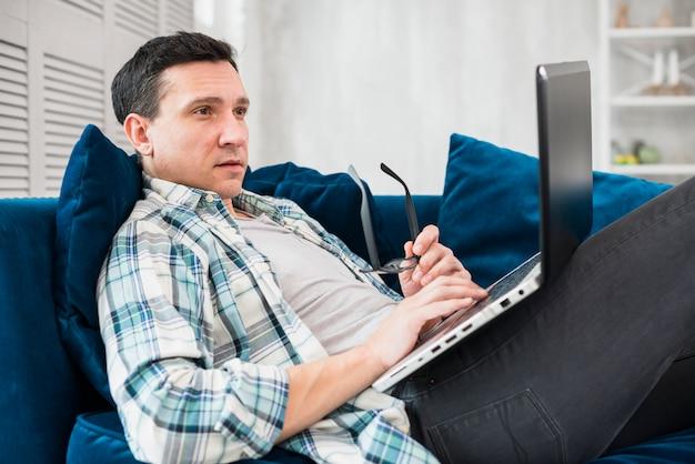 Homem, usando, laptop, ligado, canapé Foto gratuita