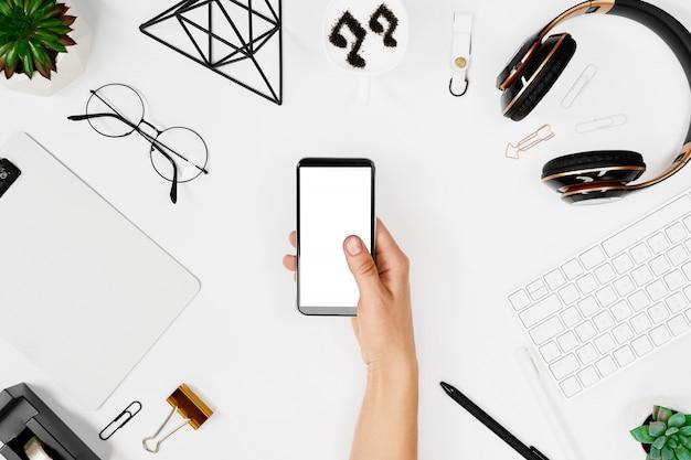 Homem usando o telefone sobre a maquete do espaço de trabalho criativo Foto Premium