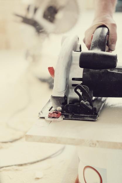Homem usando serra elétrica na carpintaria Foto gratuita