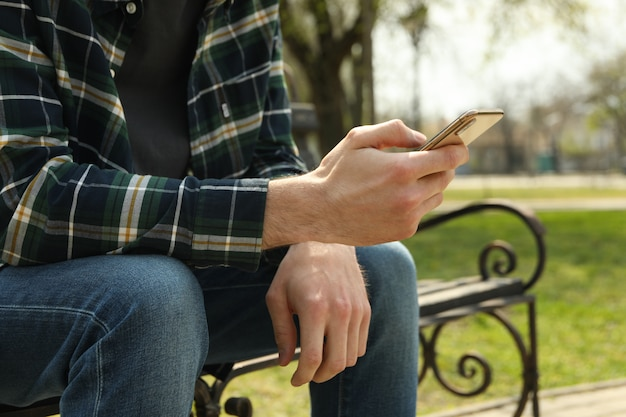 Homem usando smartphone sentado no banco do parque Foto Premium