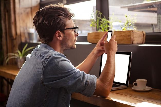 Homem usando smartphone sentado Foto Premium