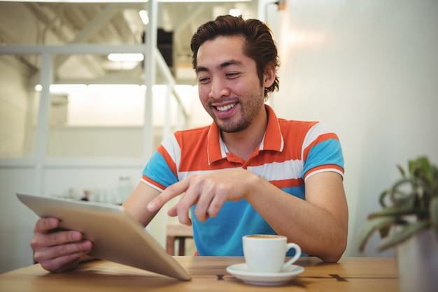 Homem usando tablet digital com xícara de café na mesa Foto gratuita