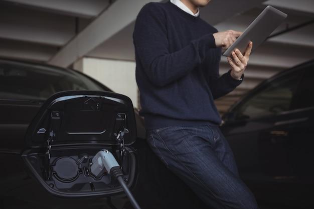 Homem usando tablet digital enquanto carrega carro elétrico Foto gratuita