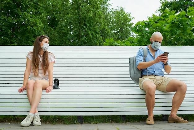 Homem usando telefone e jovem mulher sentada em extremos opostos de um banco, mantendo distância um do outro para evitar a propagação do coronavírus. Foto Premium