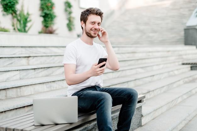 Homem, usando, telefone, e, laptop, ligado, a, banco Foto Premium