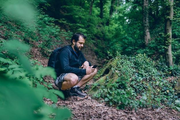 Homem usando telefone inteligente para navegar na floresta Foto Premium