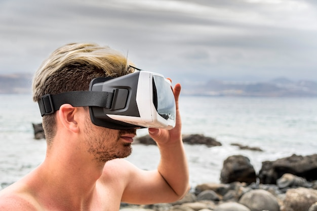 Homem usando um fone de ouvido da realidade virtual na praia Foto Premium