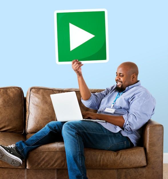 Homem usando um laptop e segurando um botão de play Foto gratuita