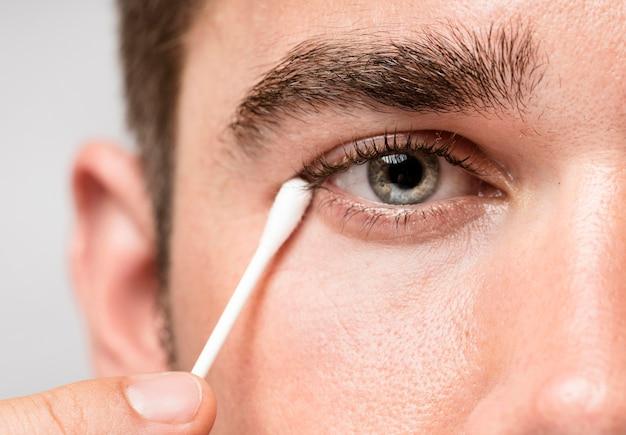 Homem usando um palito para limpar o olho Foto gratuita