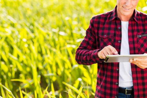 Homem usando um tablet em um campo de milho Foto gratuita