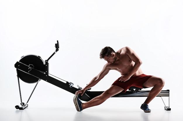 Homem usando uma máquina de imprensa em um clube de fitness. Foto gratuita