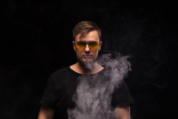 Homem vape. retrato de um homem barbudo em um close-up de fundo preto. Foto Premium
