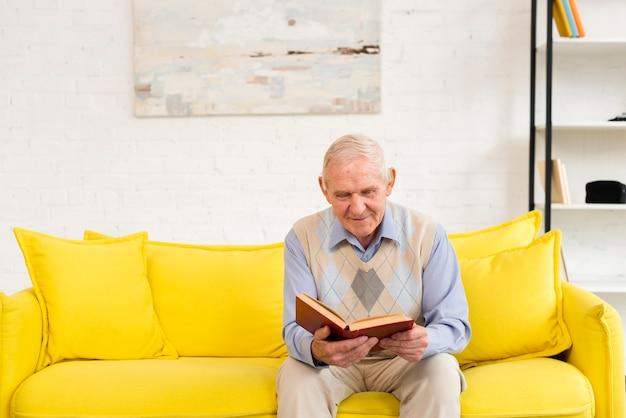 Homem velho, lendo um livro Foto gratuita