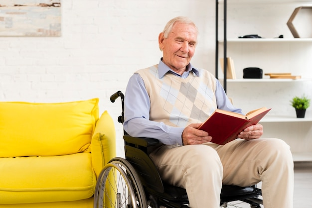 Homem velho, sentar-se cadeira rodas, enquanto, leitura, livro Foto gratuita