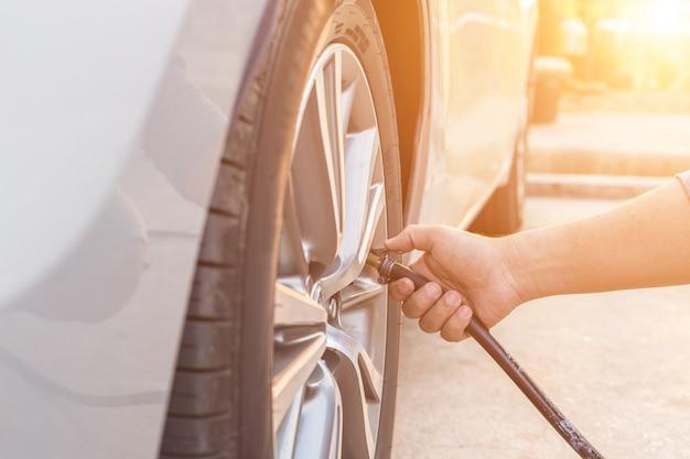 Homem, verificar, pressão ar, e, ar enchendo, para, a, pneus, de, seu, car Foto Premium