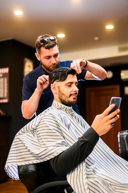 Homem, verificar, telefone, enquanto, obtendo, um, corte cabelo Foto gratuita