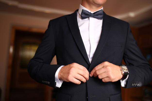Homem vestido afiado, vestindo jaqueta e gravata borboleta Foto Premium