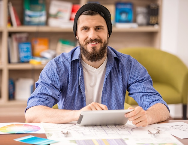 Homem vestido casual sentado à mesa e usando tablet digital Foto Premium