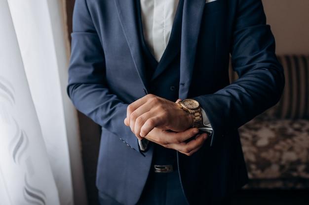 Homem vestido com o elegante terno azul, que está colocando um relógio elegante Foto gratuita
