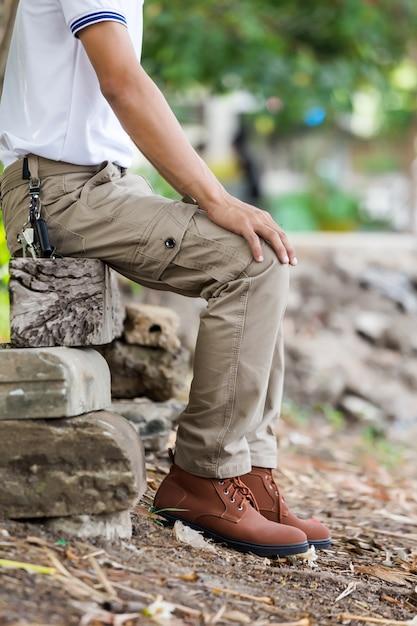 Homem vestindo calças cargo marrom e sentado no parque natural Foto Premium