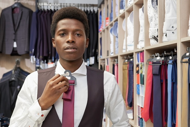 Homem vestindo camisa branca, colete preto, escolhendo a gravata. Foto gratuita